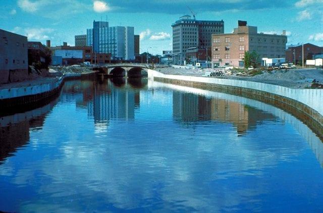 A calm river flows through an urban area, channeled between cement banks.
