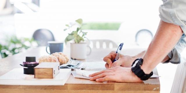 Man signing documents; image by rawpixel, via Unsplash.