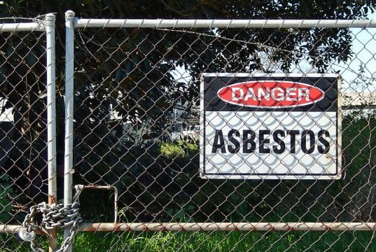 "Chain-link gate with a ""Danger – Asbestos"" sign; image by Michael Coghlan, via Flickr, CC BY-SA 2.0, no changes."