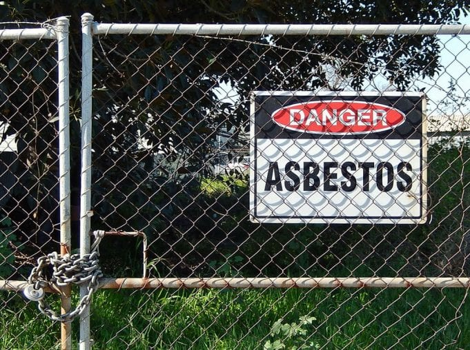 """Chain-link gate with a """"Danger – Asbestos"""" sign; image by Michael Coghlan, via Flickr, CC BY-SA 2.0, no changes."""