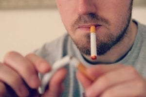Man smoking e-cigarette while breaking a traditional cigarette in half; image by Vaping360.com, via Flickr, CC BY 2.0, no changes.