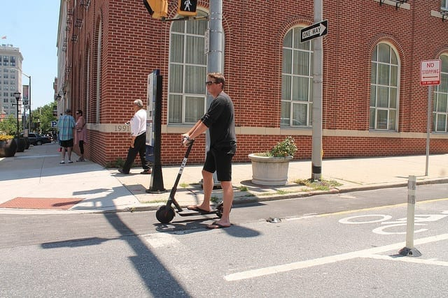 Man riding electric scooter; image by Elvert Barnes, via Flickr, CC BY-SA 2.0, no changes.