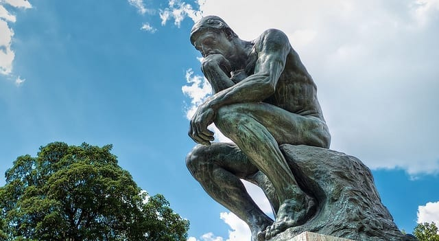 Rodin's classic statue of a man in thoughtful repose, photographed fro below, against a partly cloudy sky.