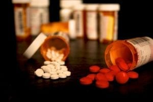 Two prescription pill bottles lie on their sides, spilling out reddish and white pills. Other pill bottles sit in the distance.