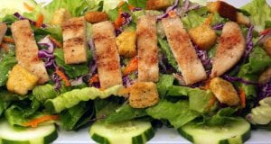 Image of cooked chicken ontop of a salad