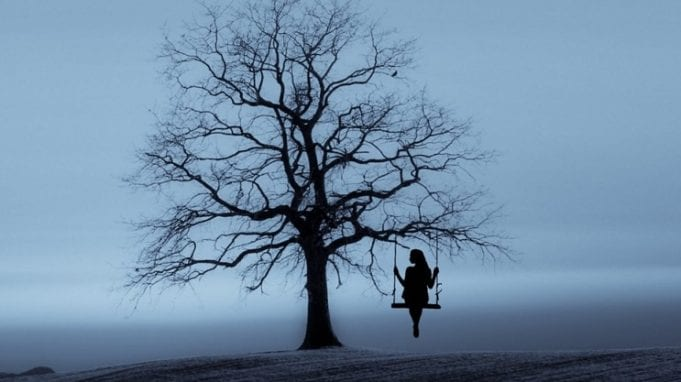 A lone figure sits on a swing that hangs from a bare tree, all in dark silhouette against a grey background.