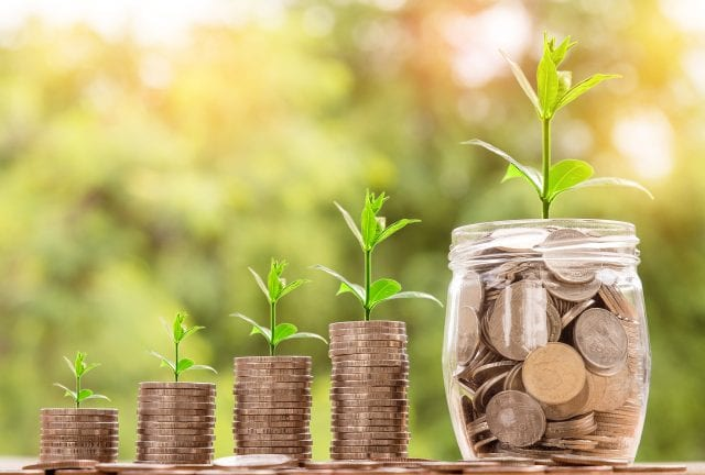Plants growing out of coins, indicating growth of investments; image by nattanan23, via Pixabay, CC0.