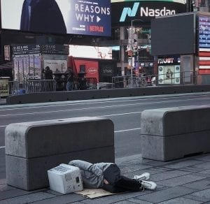 One of the many anonymous people who sleep on our sidewalks. A person laying on flattened cardboard, head cushioned and privacy provided by a postal service box turned on its side, with businesses in the background.