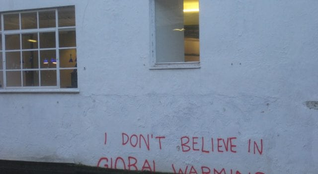 "On a white wall, partially obscured by rising flood water, are the scrawled words ""I Don't Believe in Global Warming."""