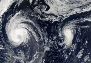 A satellite image of blue ocean and swirling cloud masses, including Hurricane Michael and a smaller Tropical Storm Leslie.