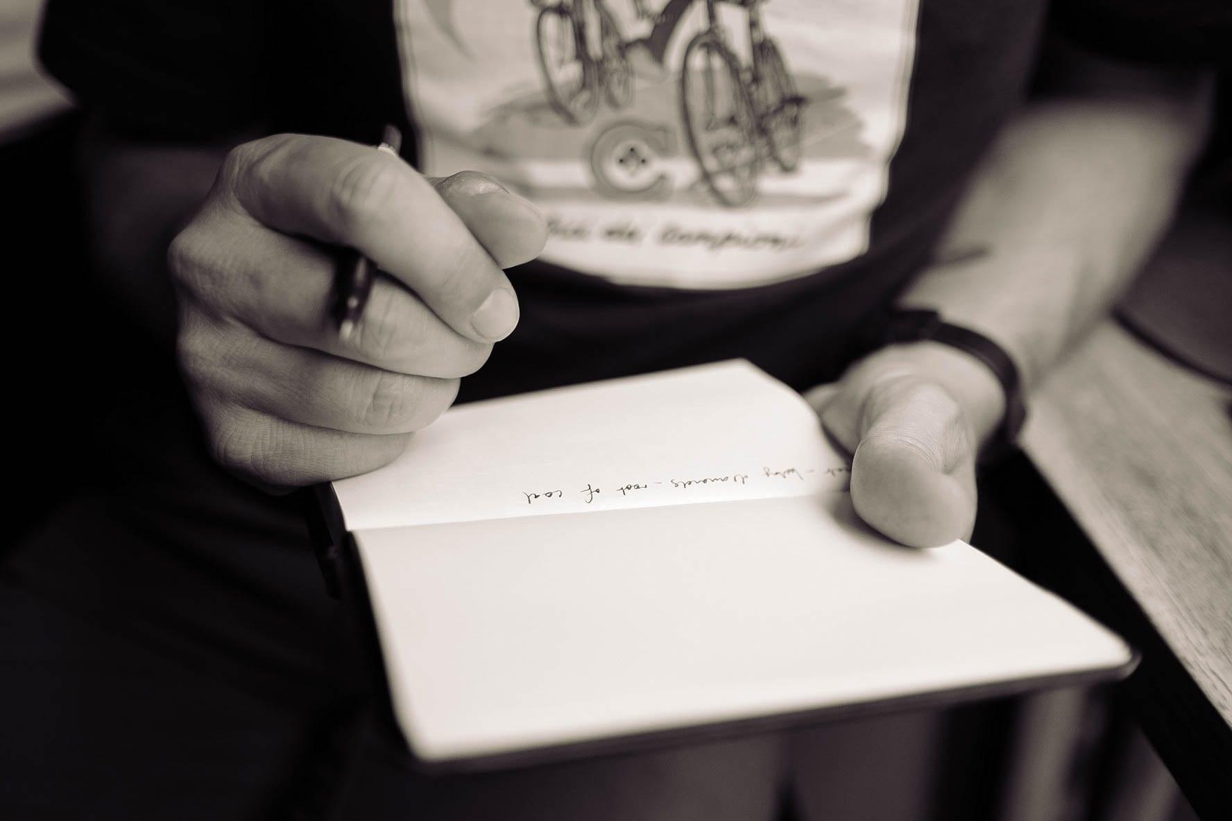 Man writing; image by Calum MacAulay, via Unsplash.com.