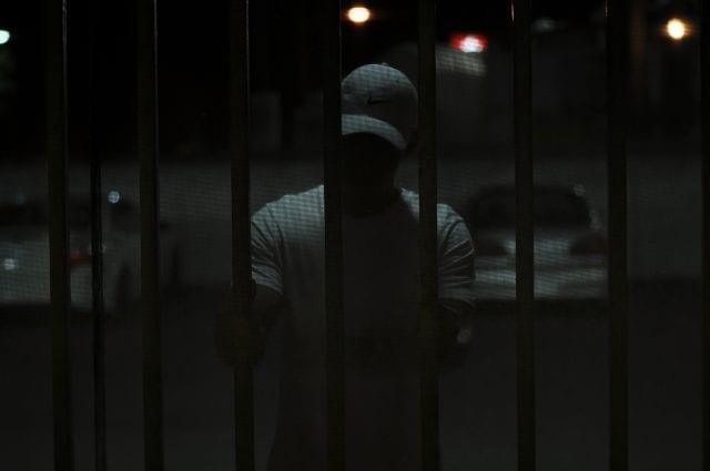 Man in cell; image by Jacky Chiu, via Unsplash.com.