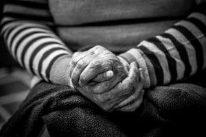 Elderly person folding their hands
