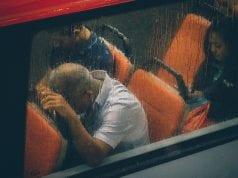 Man sleeping on train; image by Lily Banse, via Unsplash.com.
