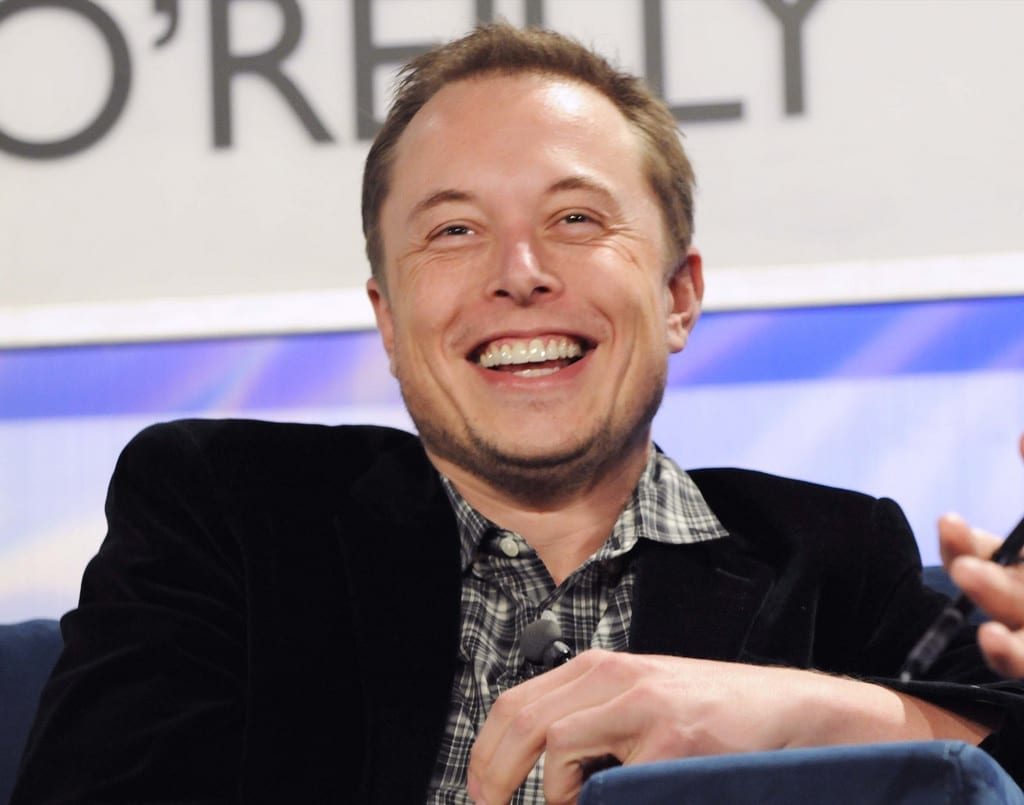 Elon Musk, grinning and at ease, wearing a dark suit and a plaid shirt with an unbuttoned collar.
