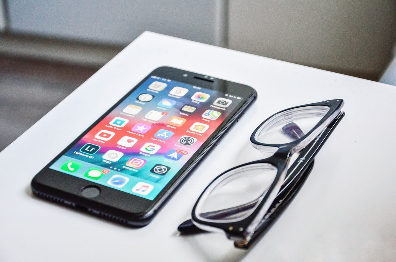 Smartphone displaying apps next to a pair of eyeglasses; image by David Švihovec, via Unsplash.com.