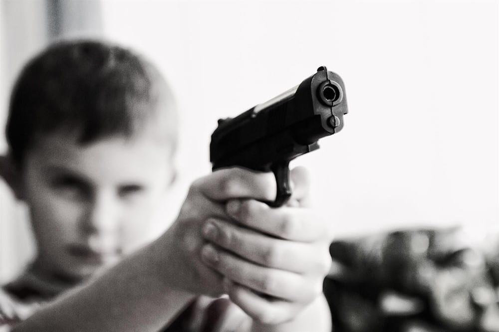 Boy with gun; image by jarmoluk, via Pixabay.com, CC0.