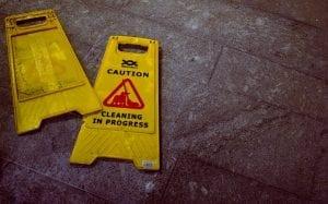 """Caution: Cleaning in Progress"" signs lying on tile floor; image by Oliver Hale, via Unsplash.com."