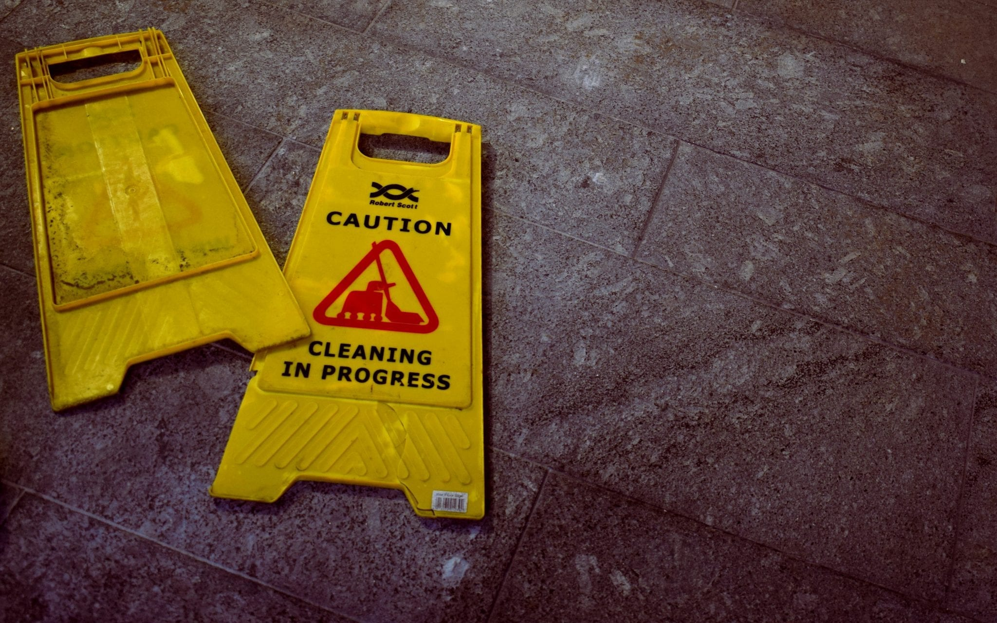 """Caution: Cleaning in Progress"" signs lying on tile floor; image by Oliver Hale, via Unsplash.com."