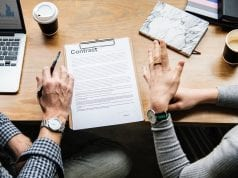 Man and woman reviewing contract; image by Rawpixel, via Unsplash.com.