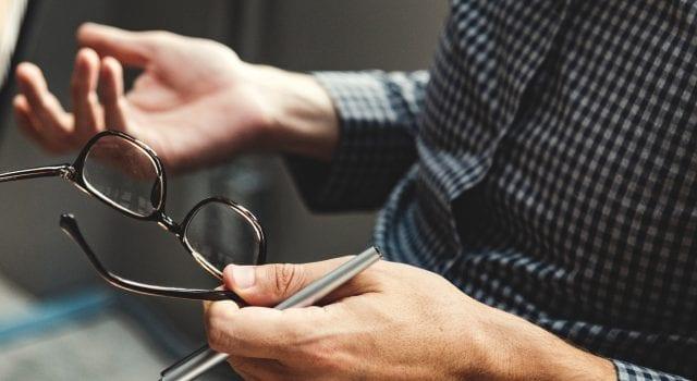 Person holding eyeglasses; image by Rawpixel, via Unsplash.com.