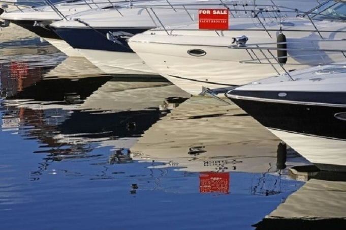 Boat with a for sale sign; image from Shutterstock, purchased by author.