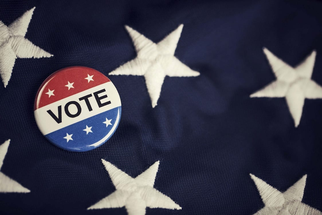 "A red, white, and blue button that says ""VOTE"" lies atop the starry blue field of an American flag."