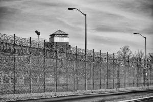 Black and white picture of a prison from outside the fence; image by Brad.K, via Flickr, CC BY 2.0, no changes.