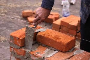 A man's hand spreads mortar with a trowel as he builds a wall from common red bricks.
