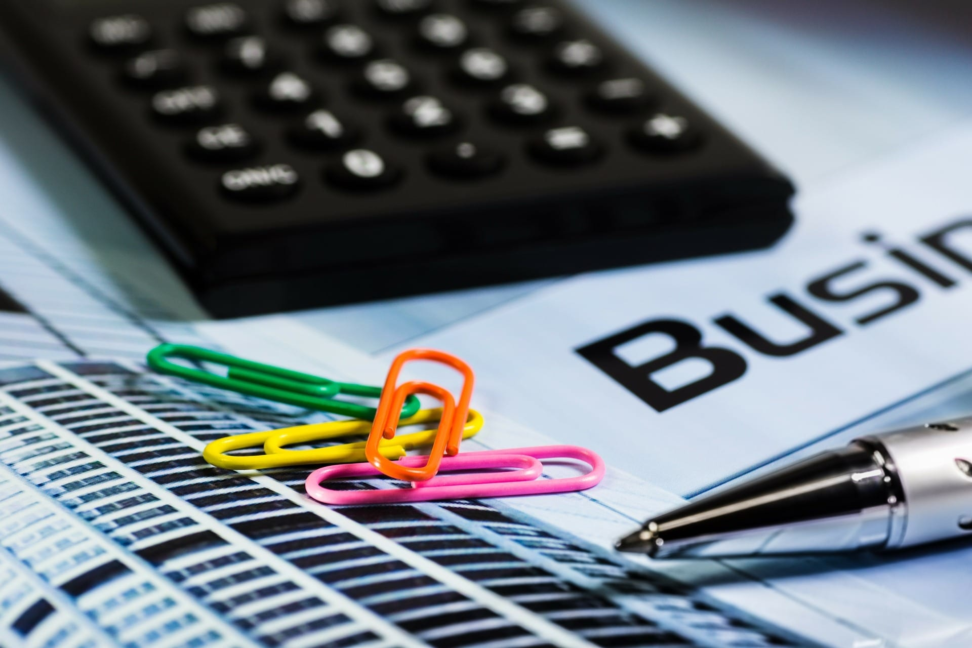 Brightly colored paper clips with business papers, calculator, and pen; image by Alexander Stein, via Pixabay.com, CC0.