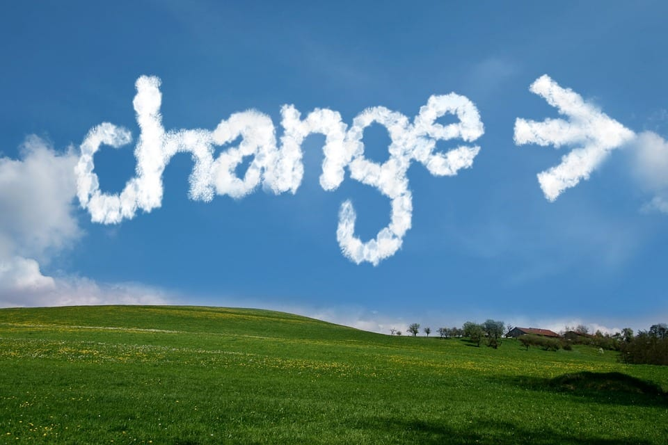 A green, grassy hill with a big blue sky. Among few clouds, the word CHANGE is written in white, puffy letters, with an arrow pointing to the right.