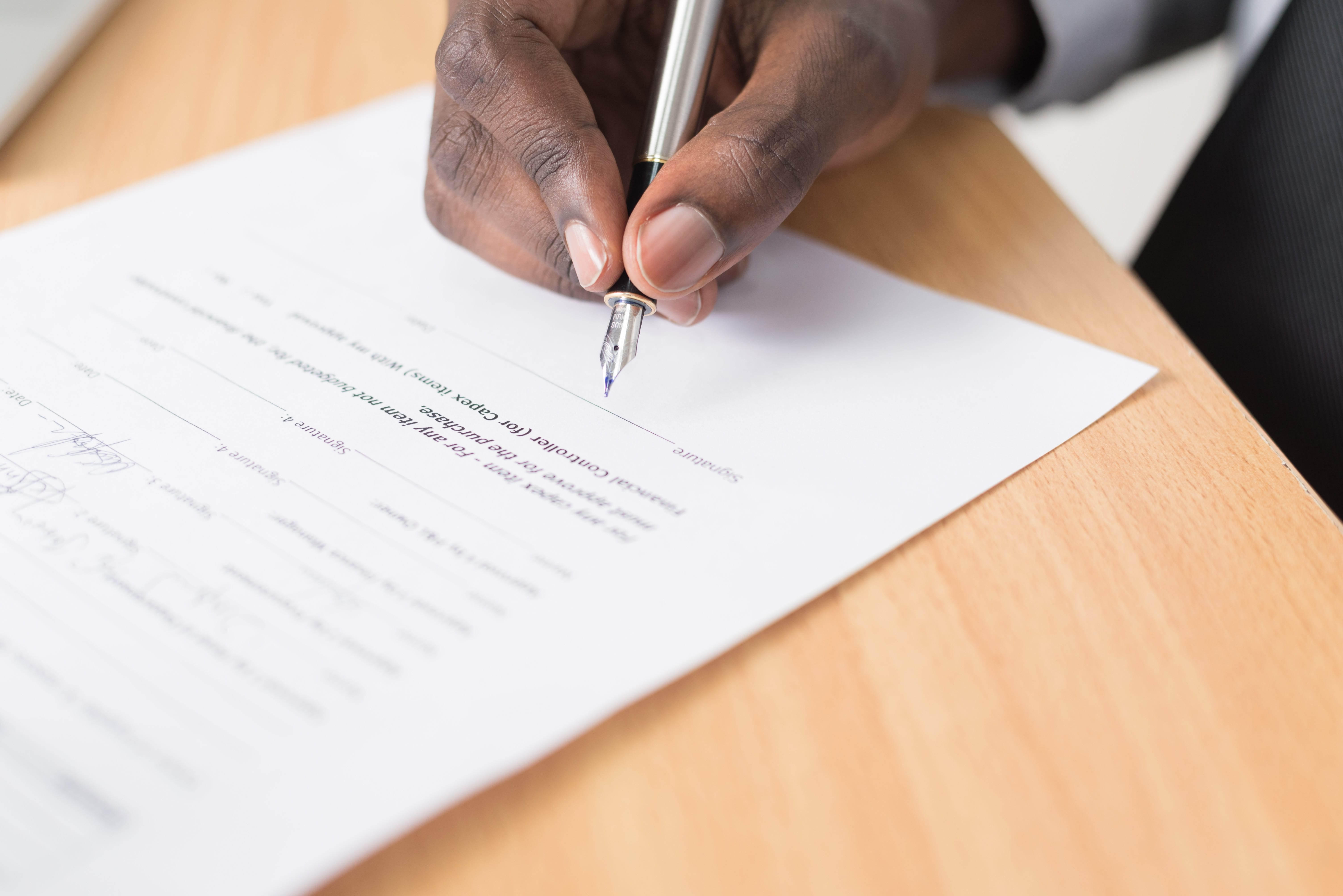 Man signing paperwork with a fountain pen; image by Cytonn Photography, via Unsplash.com.