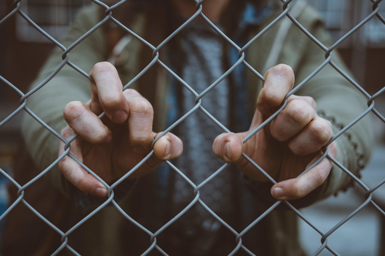 Man grabbing chainlink fence, image by Mitch Lensink, via Unsplash.com.