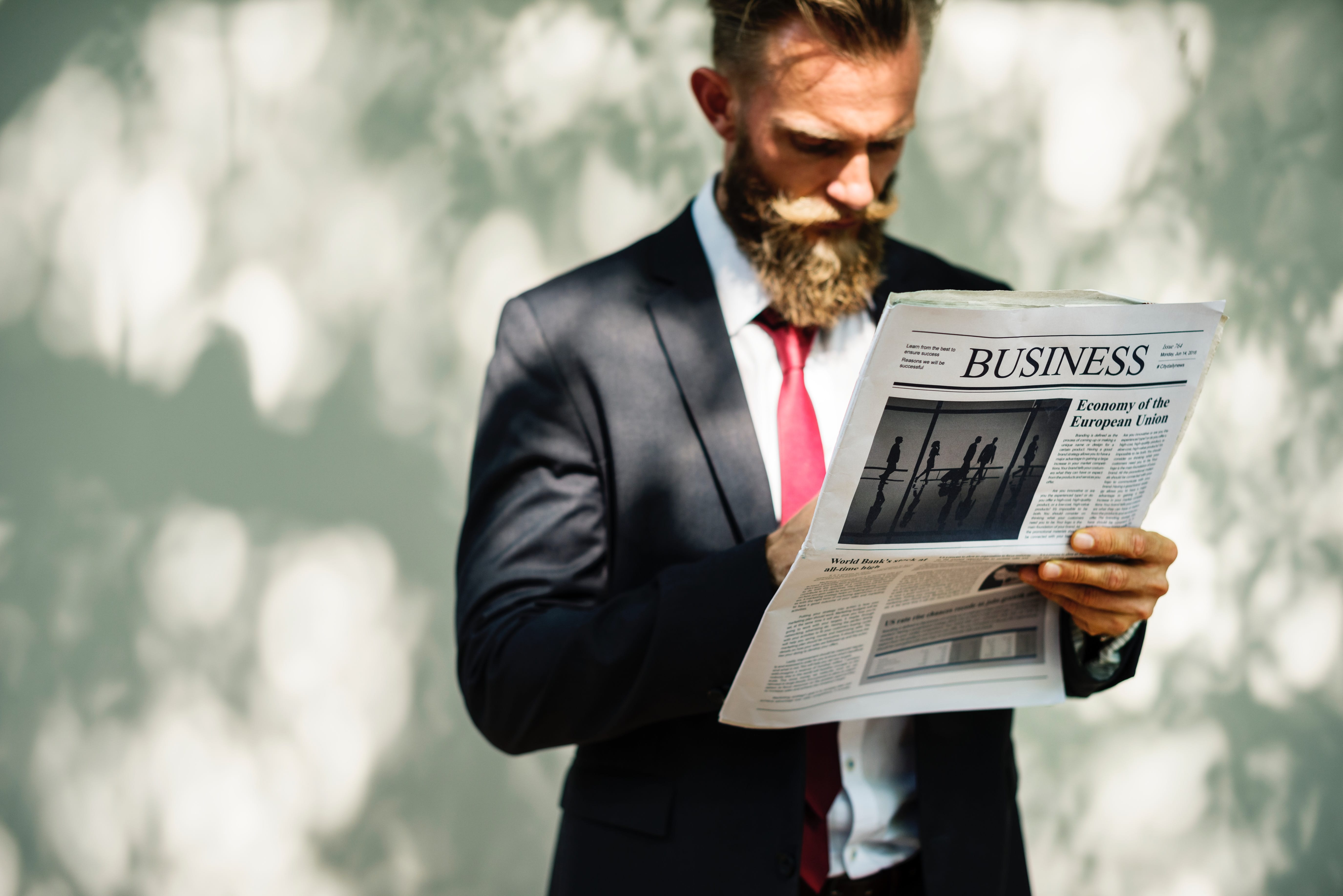 Man reading business section of newspaper; image by Rawpixel, via Unsplash.com.