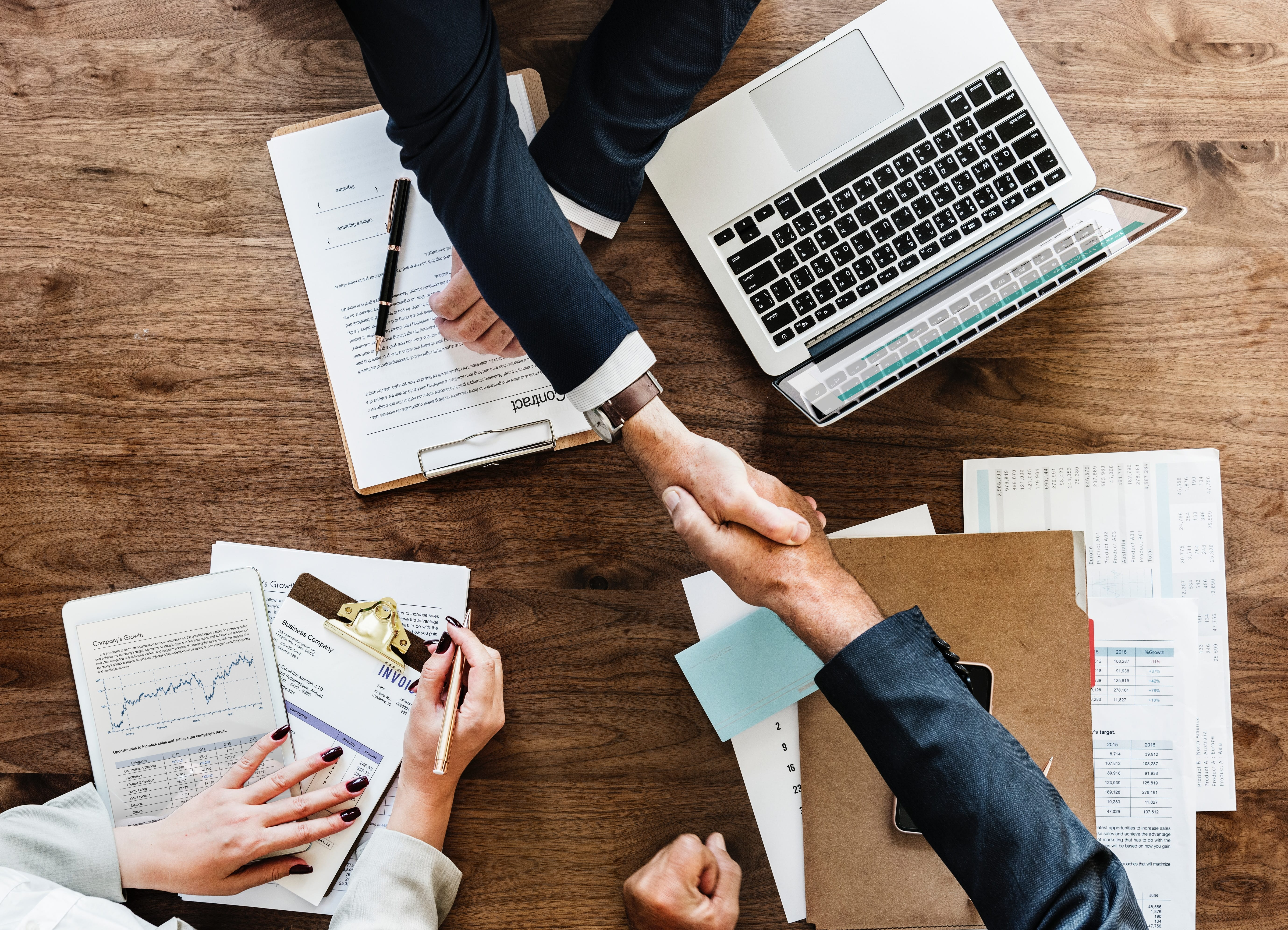 People shaking hands over a table with paperwork and a laptop computer; image by Rawpixel, via Unsplash.com.