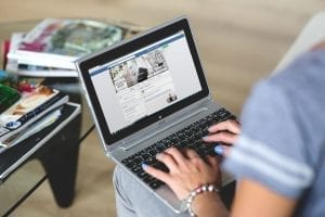 Woman viewing Facebook on a laptop computer; image via Pexels.com.