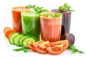 Four glasses of various fresh juices, surrounded by cut vegetables; image via PxHere.com, CC0.
