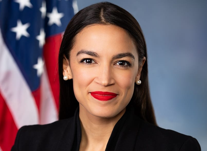 A smiling Alexandria Ocasio-Cortez poses in front of the American Flag in her official House portrait in 2018.