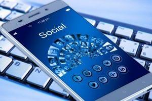 Smartphone displaying social media on top of a computer keyboard; image by geralt, via Pixabay.com, CC0.