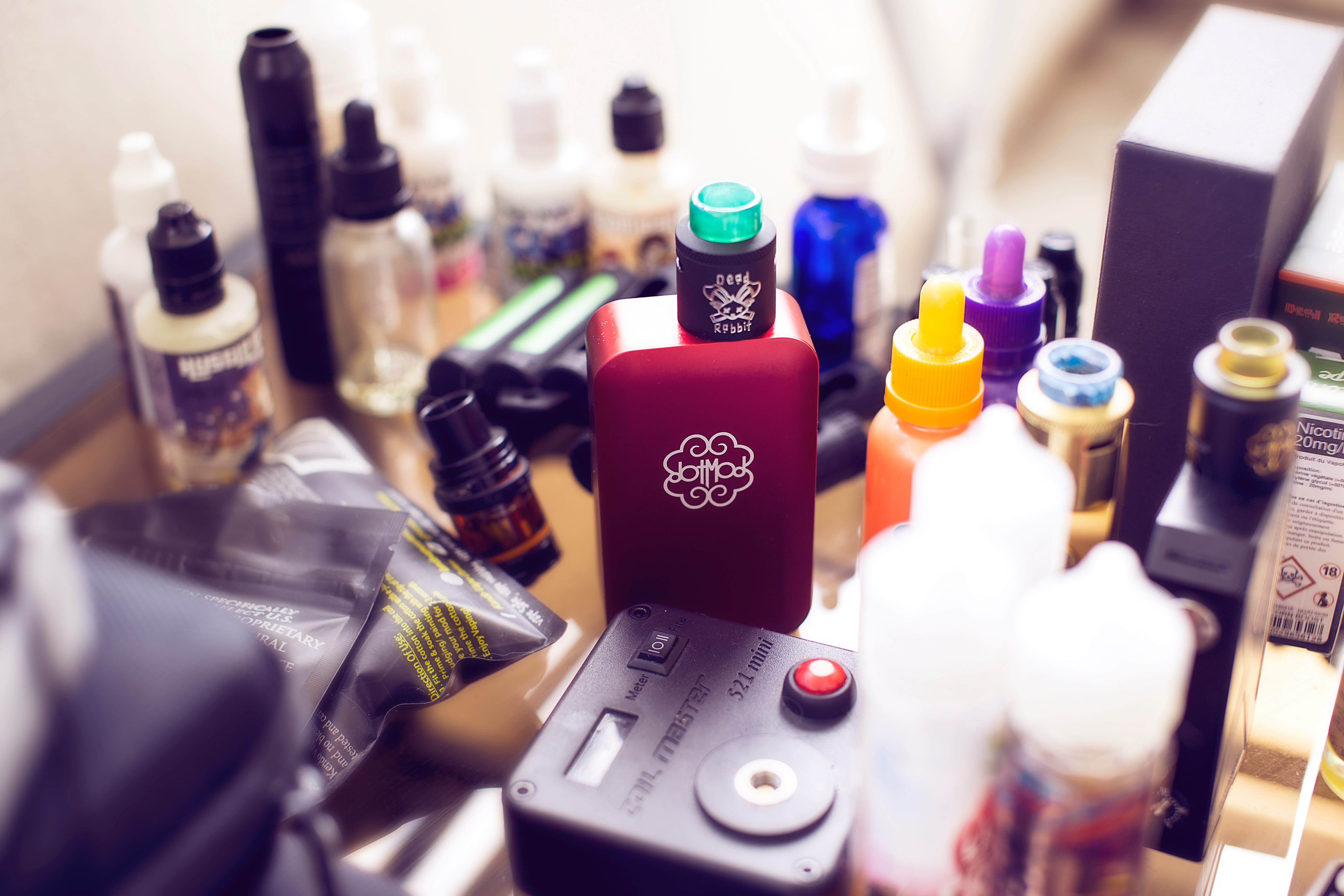 Red box mod vape beside e-juice bottles; image by Antonin FELS, via Unsplash.com.