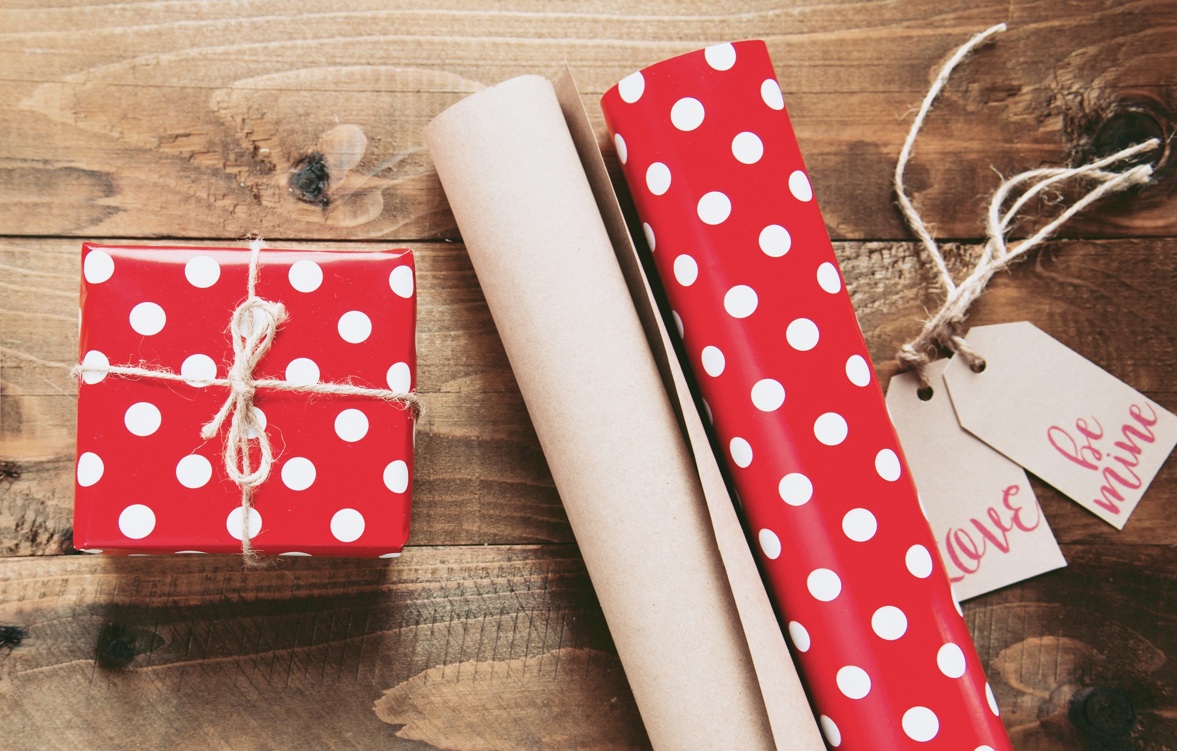 """Box wrapped in red paper with white dots sitting next to wrapping paper and gift tags saying """"Love"""" and """"Be mine."""" Image by Miroslava, via Unsplash.com."""