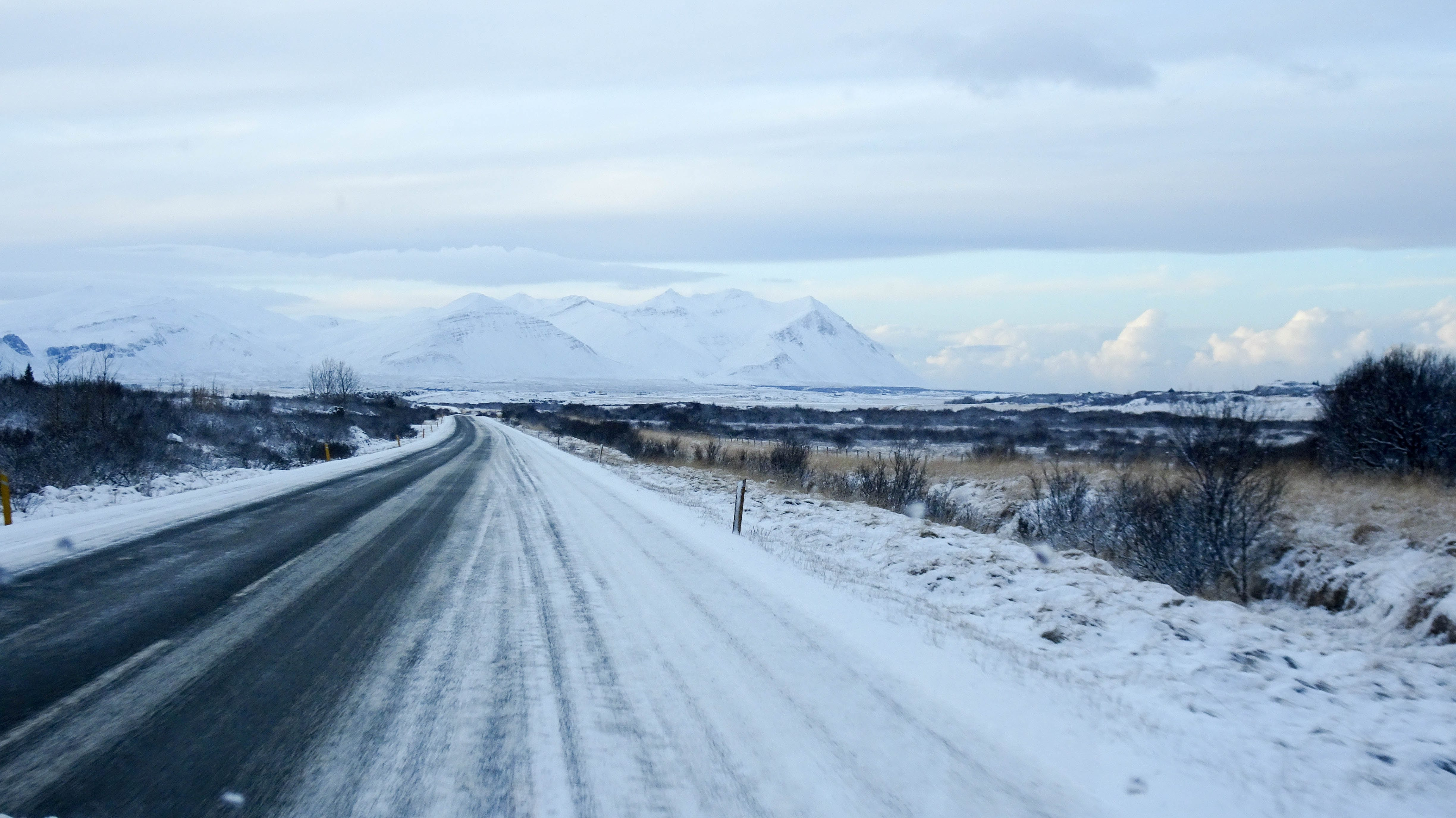 Snow-covered road flanked by fields with mountains in the distance; image by Patrick Wittke, via Unsplash.com.