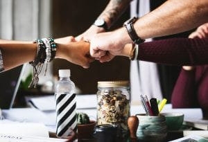 Fist bumps during team meeting; image by Rawpixel, via Unsplash.com.