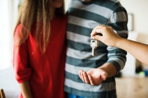 Man and woman being handed keys to a new home; image by Rawpixel, via Unsplash.com.