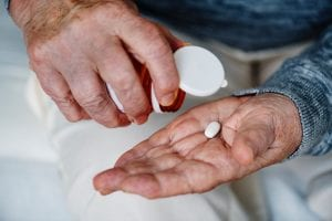 Man dispensing a white, oval-shaped pill from a bottle into his hand; image by Rawpixel, via Unsplash.com.