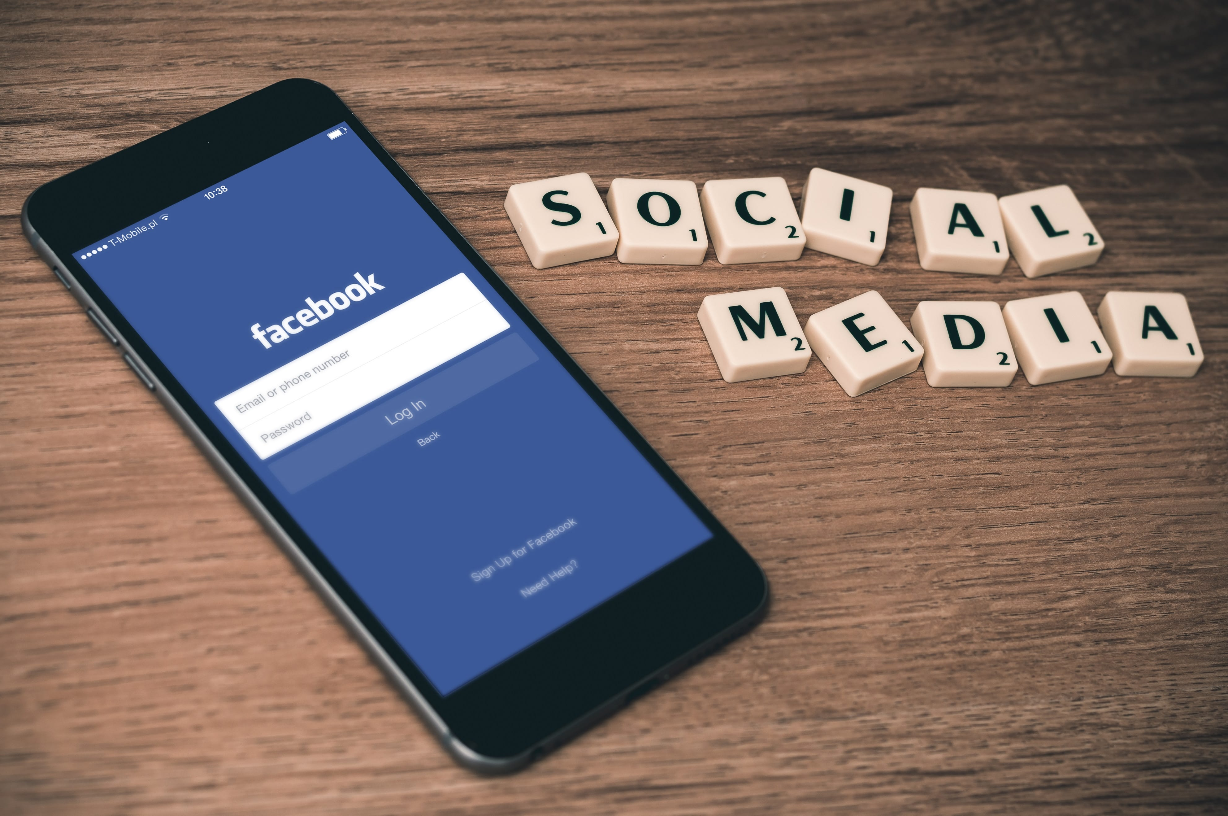 "Smartphone showing Facebook login screen with the words ""Social Media"" spelled out next to it in Scrabble tiles; image by William Iven, via Unsplash.com."