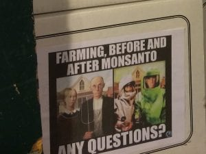 "Flyer saying ""Farming, before and after Monsanto. Any questions?"" with Grant Wood's American Gothic on the left and a modified version with the couple wearing hazmat suits on the right. Image by Kevin Krejci, via Flickr, CC BY 2.0, no changes."