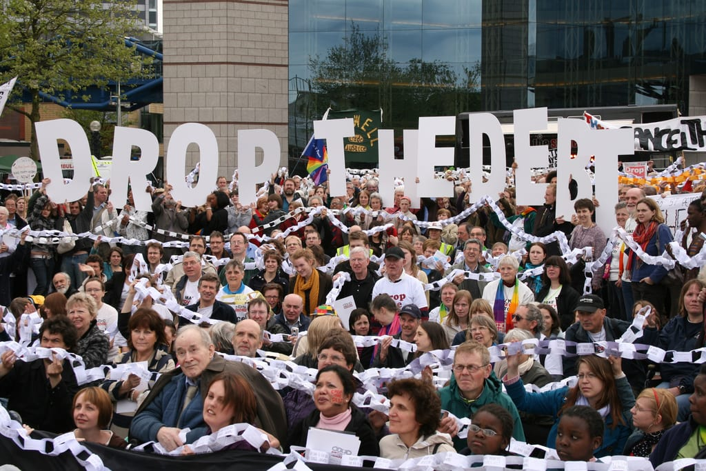 """A crowd of people, bound by paper chain links, hold up letters that spell out """"Drop The Debt."""""""