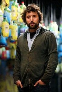 TerraCycle CEO and Loop partner Tom Szaky, hair askew, wearing a hoodie sweatshirt and standing in front of strings of plastic bottles.