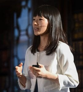 Marie Kondo speaking in front of a dark background, wearing a white cardigan and a microphone.